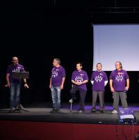 5 hombres con camisetas moradas subidos en un escenario