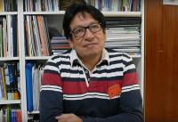 Vladimir Paspuel Revelo, presidente de la Asociación Rumiñahui, sentado frente a una biblioteca antes de una entrevista